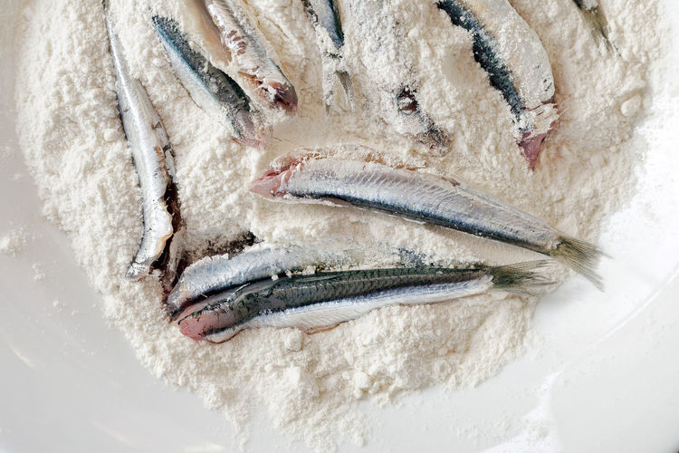 Overhead view of raw fish with flour in plate