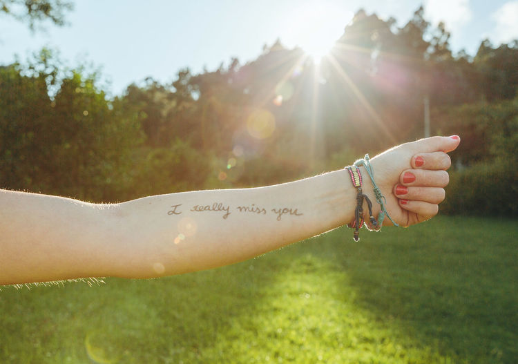 Closeup of female arm with the text -I really miss you- written in the skin over a sunny nature background Horizontal Nature Sunlight Sunny Text Writing Arm Emotion Handwriting  Human Body Part Ink Inscription Letter Message Miss Outdoors Phrase Real People Sentence Skin Summer Sun Tattoo Unrecognizable Person Words