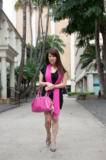 Full length of happy young woman holding pink while standing against trees
