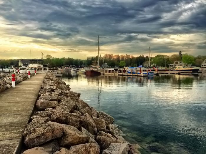 Boats in harbor against cloudy sky