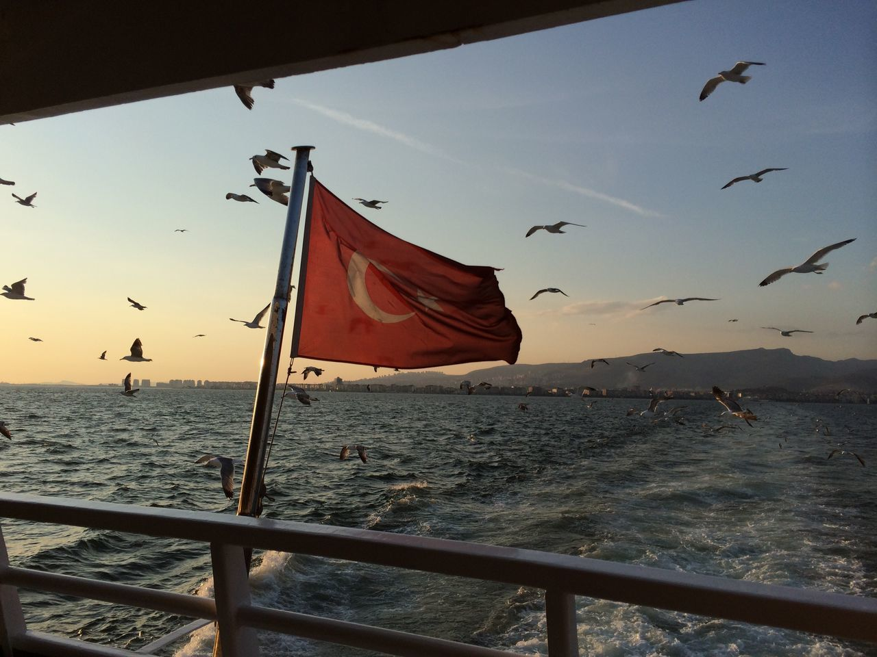 Turkish flag on boat in sea during sunset