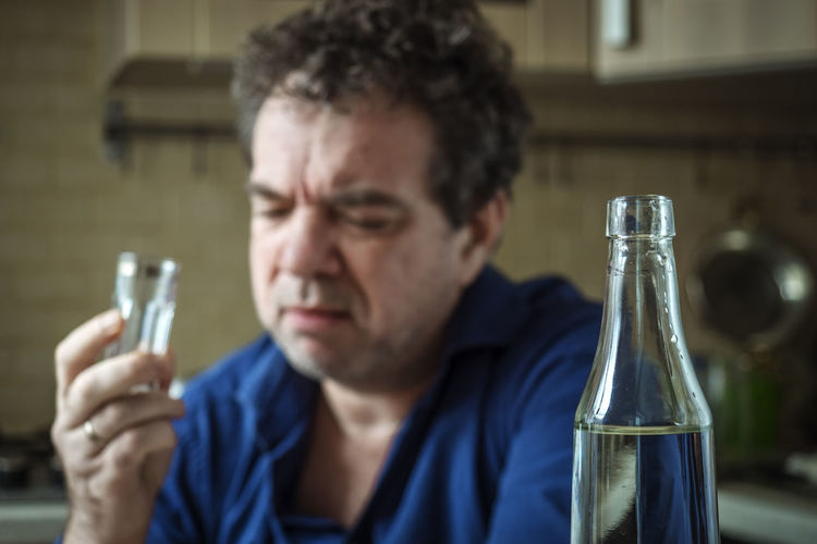 Close-up portrait of a man drinking glass
