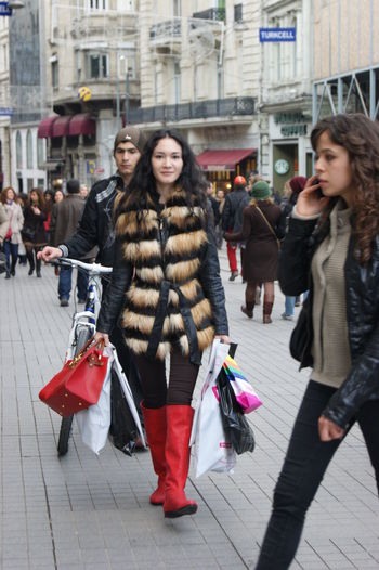 Bag Brunette Casual Clothing City Fur Jacket Leisure Activity Lifestyles Looking At Camera Real People Red Bag Red Boots Shop Shopping Smiling Standing Young Adult Young Women People And Places