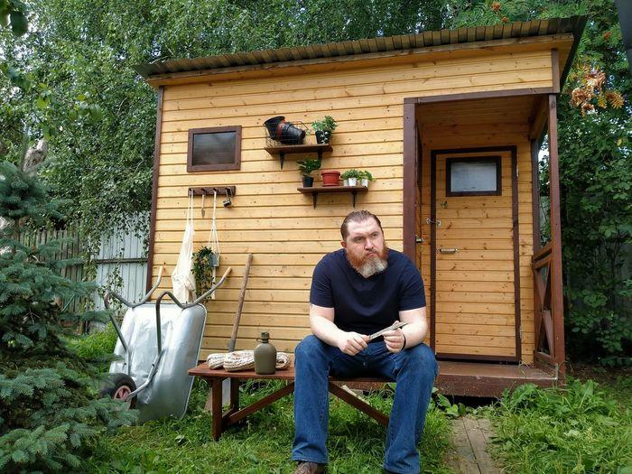 Full length of man sitting in yard against house