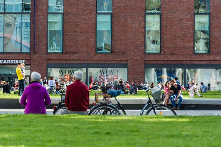 People sitting on grass in city