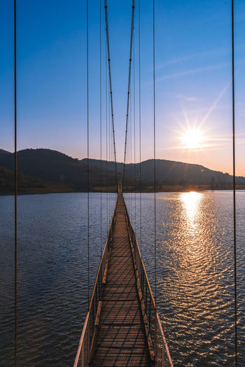 The longest suspension bridge in Bulgaria over Studen Kladenez dam with distance between the two towers of 260m. The only way to reach Lisicite village Reflection Water Sunset Nature Sky Bridge Travel Tower Lake Mountain Direction Pylon Way Suspension Dam Bulgaria Metal Overcast Wooden Suspension Bridge Longest Warm Clothing Sunlight Beauty In Nature Scenics - Nature No People Transportation Tranquil Scene Tranquility Connection The Way Forward Architecture Sun Built Structure Outdoors Diminishing Perspective Sailboat
