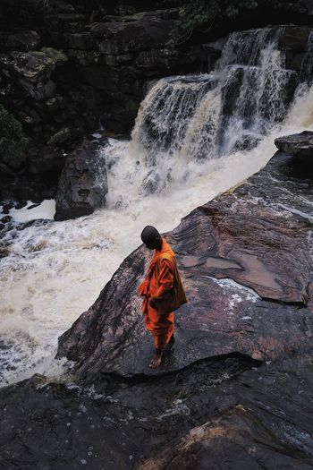 A monk gazing at a water fall at Bokor Mountain, Cambodia. Waterfall Non-urban Scene Tourism Nature Travel Destinations Cambodia