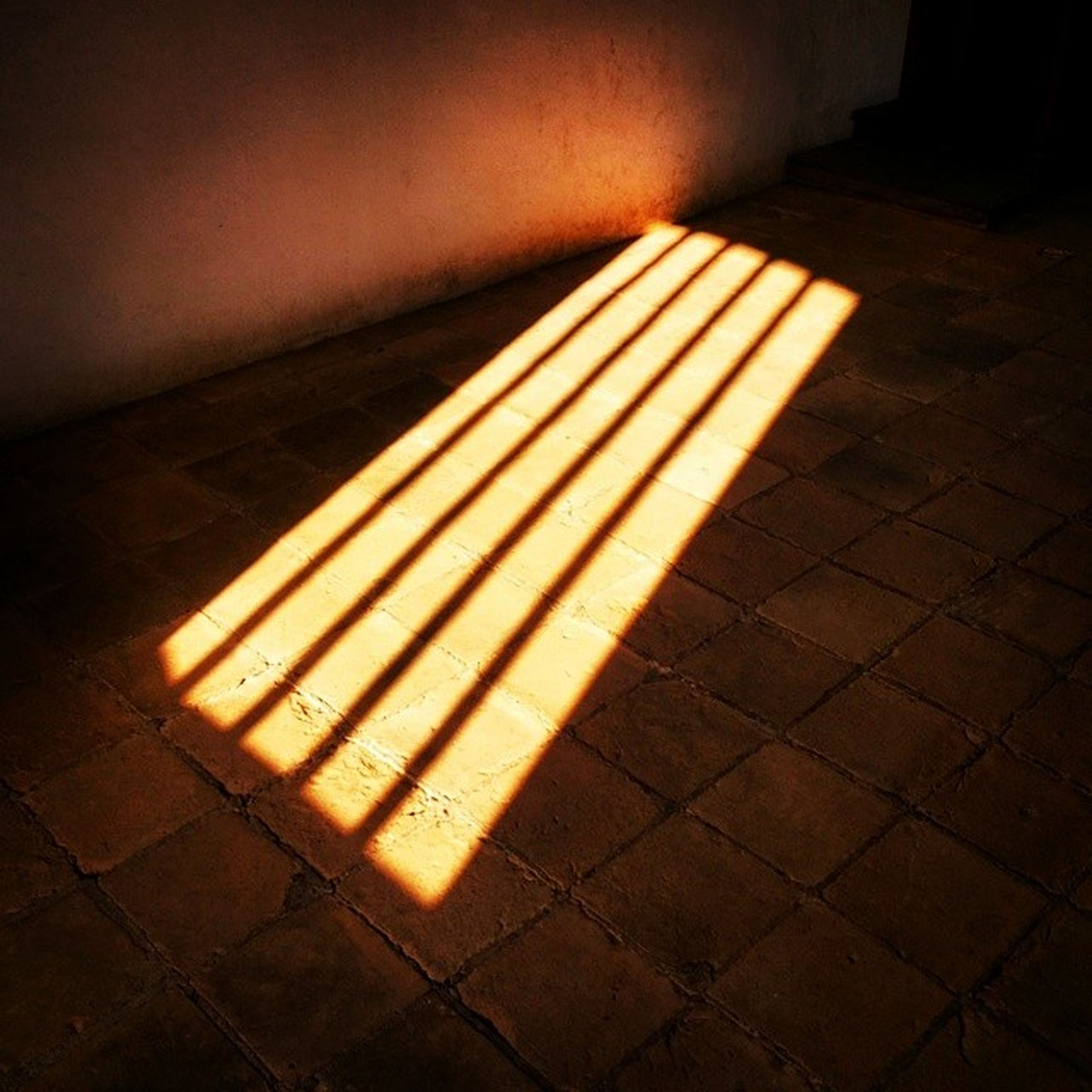 indoors, illuminated, tiled floor, pattern, shadow, wall - building feature, flooring, high angle view, empty, sunlight, night, tile, no people, sidewalk, paving stone, steps, absence, floor, yellow, footpath