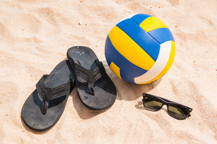 High angle view of flip-flops and ball on beach