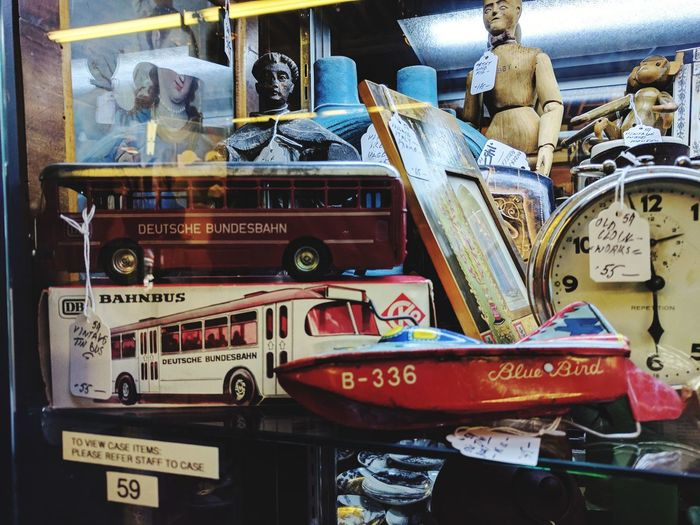 A cabinet stuffed with goodies at a vintage store Antiques Toy Boat Toy Bus No People Tin Toys Close-up Music Old-fashioned Communication Text Gramophone Arts Culture And Entertainment