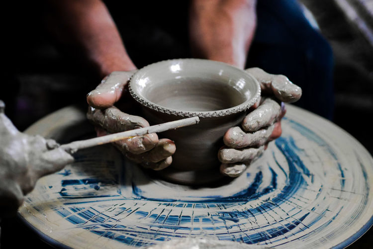 Cropped hands making clay pots