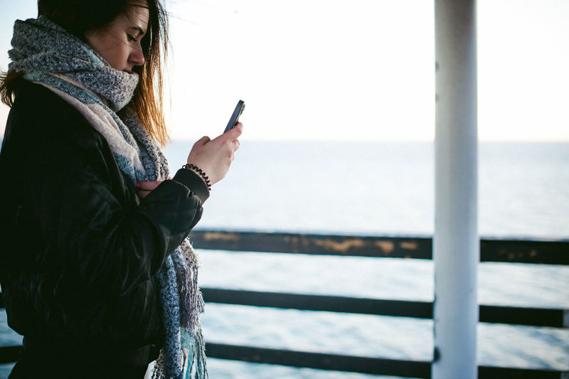 Side view of young woman using phone on pier over sea