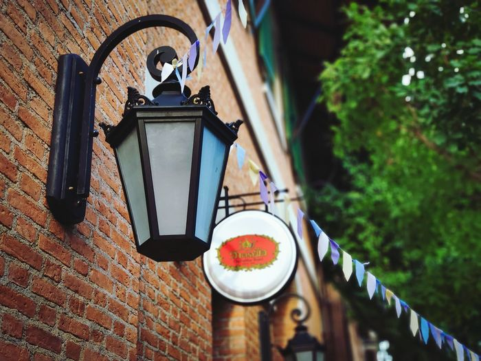 Low angle view of lantern hanging on street against building