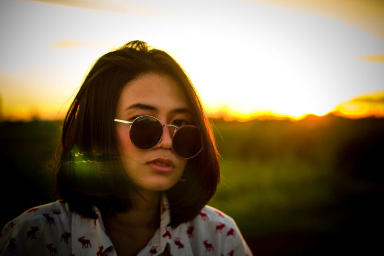 Close-Up Portrait Of Young Woman Wearing Sunglasses Against Orange Sky