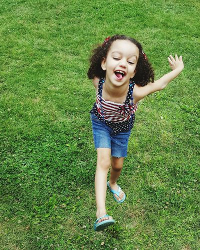 Portrait of happy girl playing on grassy field in park