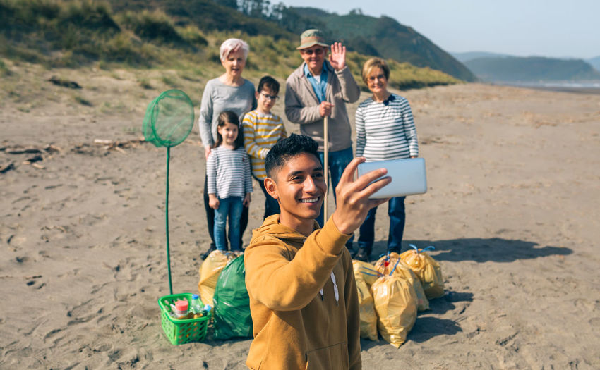 Smiling boy taking selfie with family while standing at beach