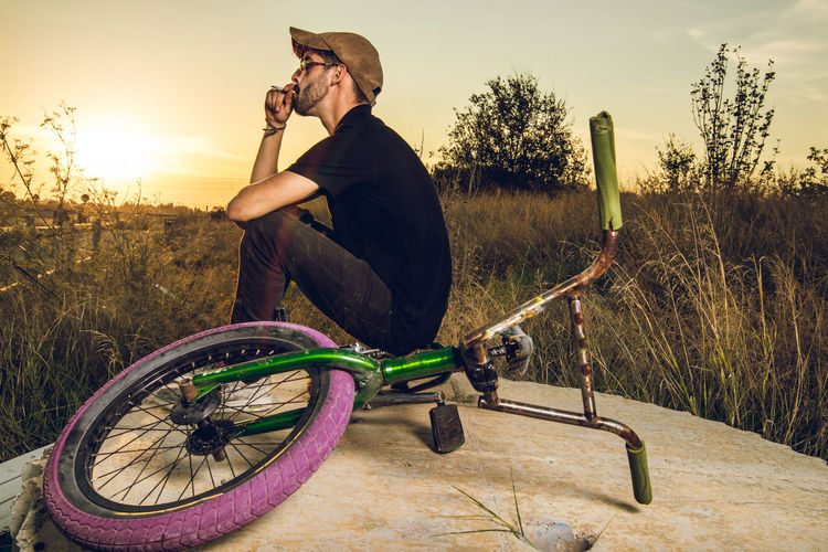 Man Sitting With Bicycle On Field Against Sky During Sunset