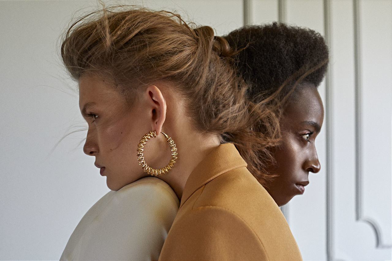Side view of young women looking away while embracing
