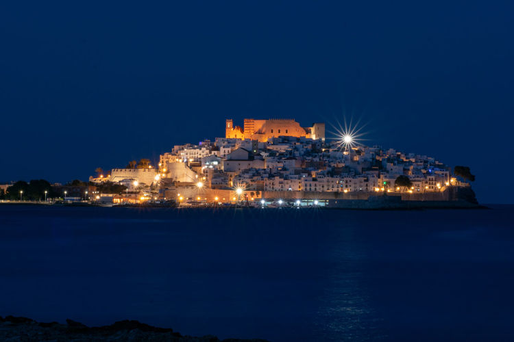 Illuminated city by sea against clear sky at night