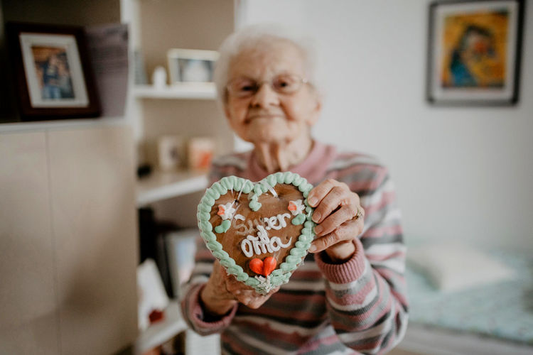 Portrait Of Senior Woman Holding Gingerbread Cookie At Home