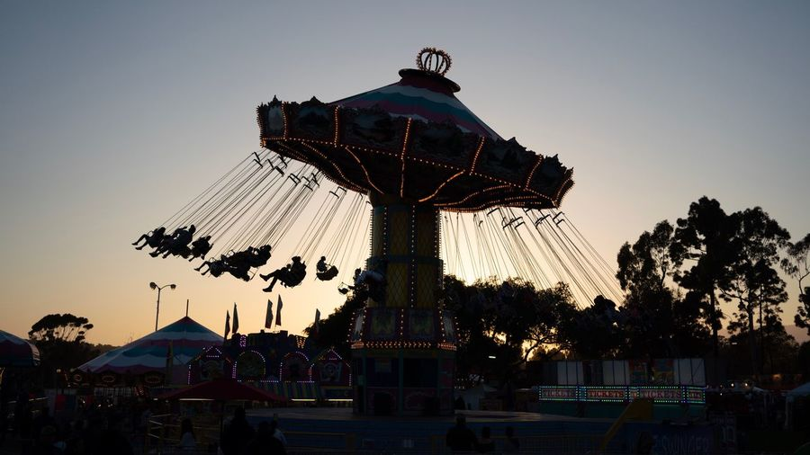 Dusk fun. Swing Fair Fun Sky Amusement Park Ride Amusement Park Arts Culture And Entertainment Nature Carousel Silhouette Sunset Outdoors Incidental People Enjoyment Large Group Of People