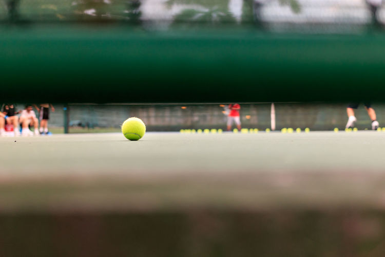 Ball on tennis court seen through railing
