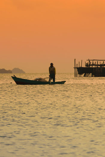 Silhouette Man In Boat On Sea Against Clear Sky During Sunset