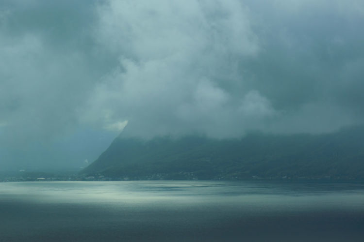 Scenic view of sea and mountains against storm clouds