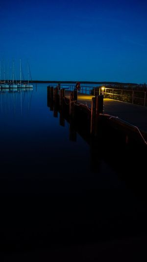 Pier on lake against clear sky at night