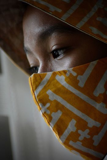 Close-up portrait of a young woman covering face