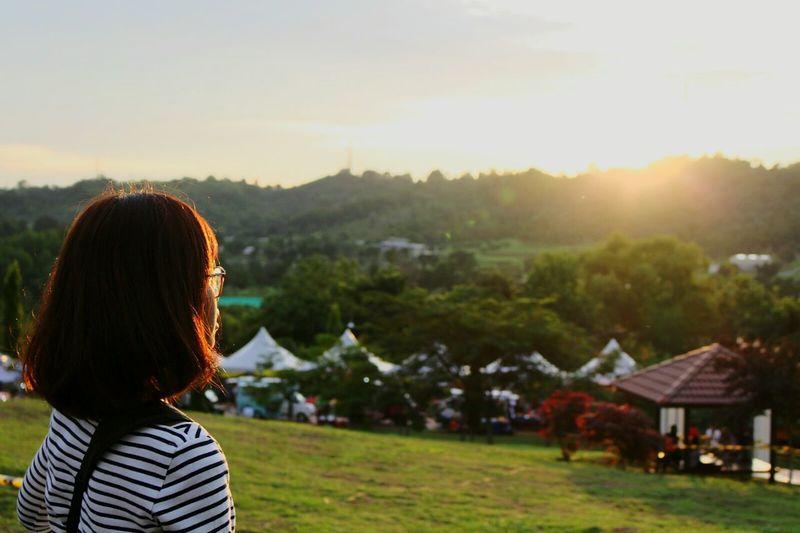 Tourists on field at sunset