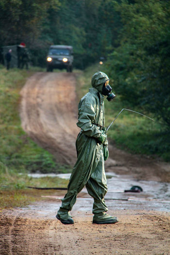 Side View Of Male Army Soldier In Protective Workwear Walking Against Trucks