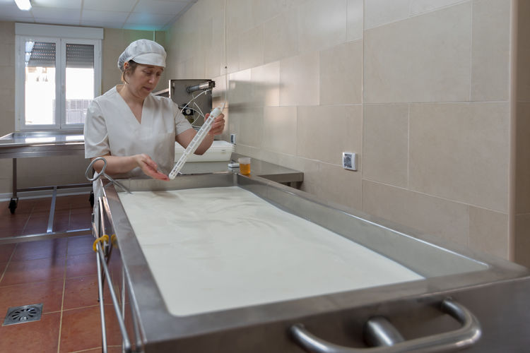 Female worker working in cheese factory