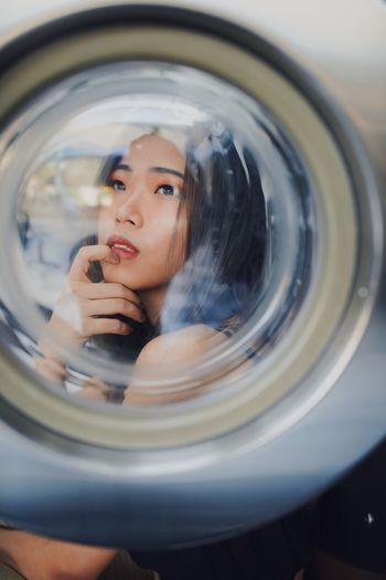 Thoughtful young woman seen through washing machine glass