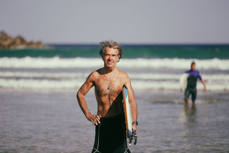 Portrait of shirtless man standing at beach against sky
