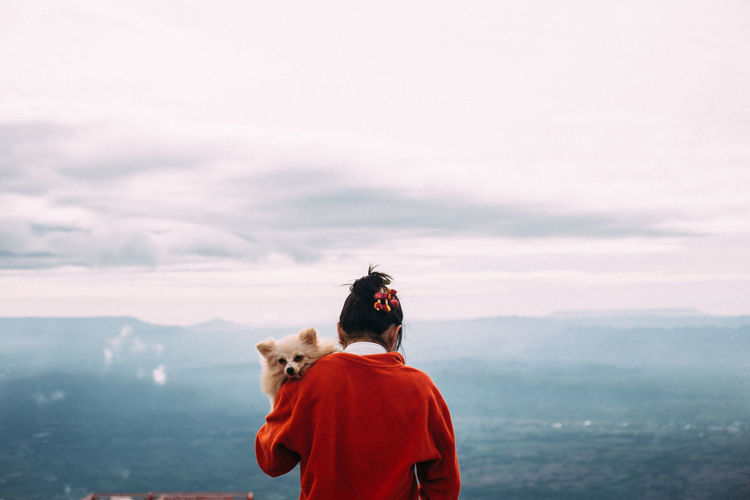 Rear view of woman with dog against sky