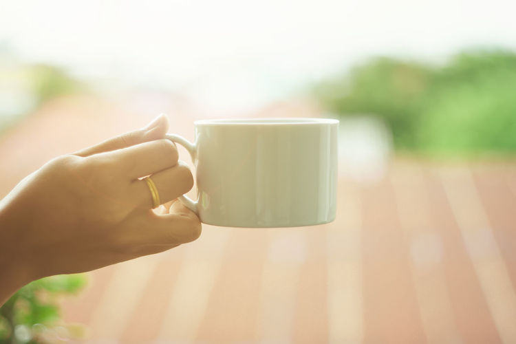 Morning coffee concept. People holding a cup of coffee drinks in the morning after wake-up. Body Part Close-up Coffee Coffee Cup Cup Day Drink Finger Focus On Foreground Hand Holding Human Body Part Human Finger Human Hand Human Limb Lifestyles Mug One Person Real People Refreshment Tea Cup