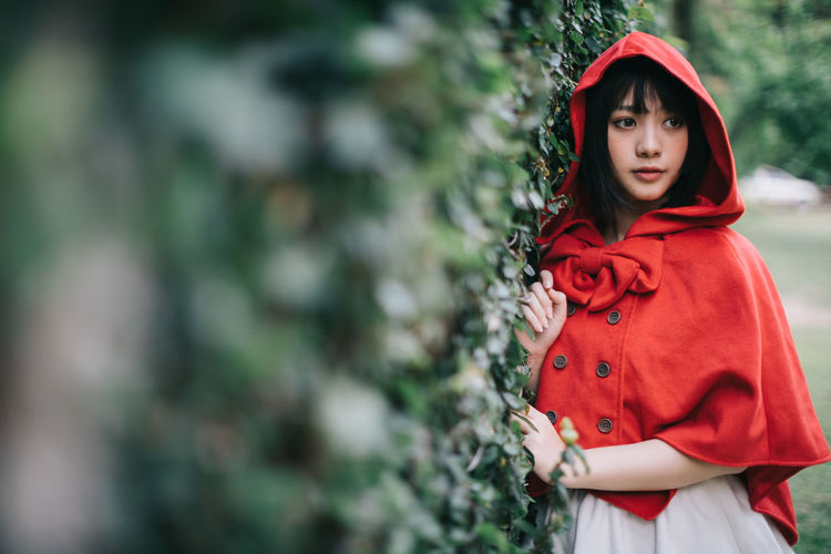 Woman in little red riding hood costume standing by plants