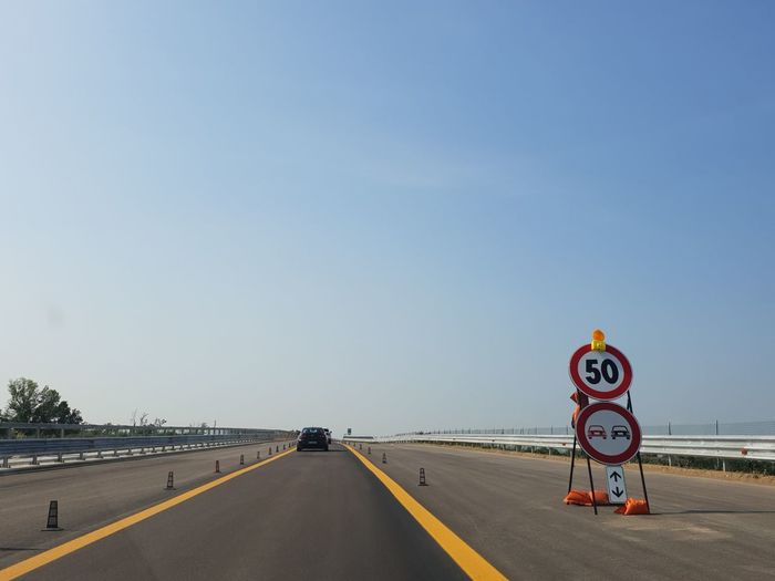 Diminishing perspective of road against clear sky