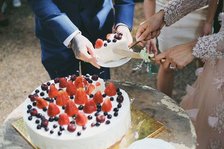Close-Up Of Hands Cutting Wedding Cake