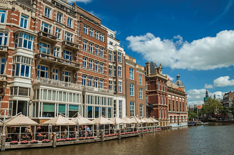 Canal with typical brick building and restaurant in amsterdam. the netherland capital full of canals