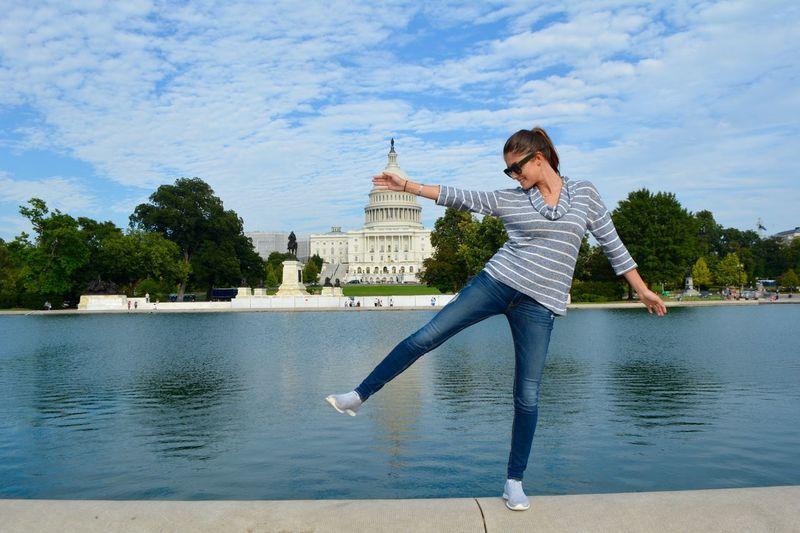 Full length of woman dancing against lake and sky