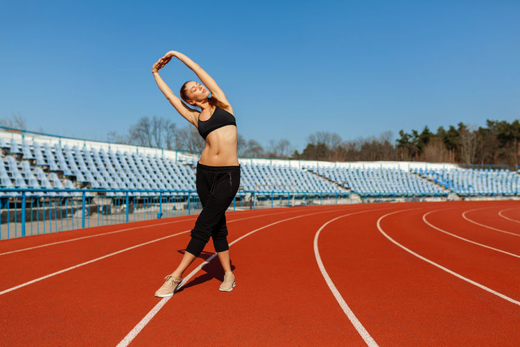 Full length of woman exercising on sports track