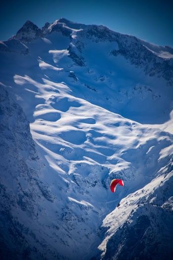 Paragliding Adventure Beauty In Nature Cold Temperature Day High Angle View Leisure Activity Mountain Mountain Range Nature One Person Outdoors People Real People Red Scenics Ski Holiday Sky Snow Snowcapped Mountain Sport Tranquil Scene Tranquility Vacations Winter
