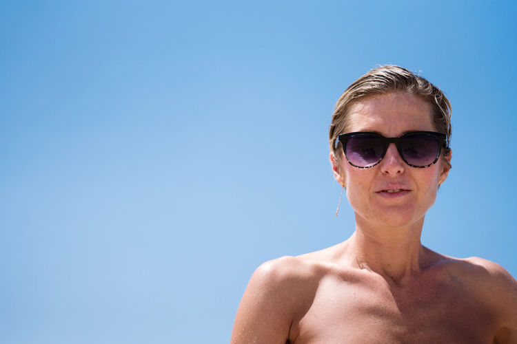 Low angle view woman with short hair enjoying sunshine wearing sunglasses