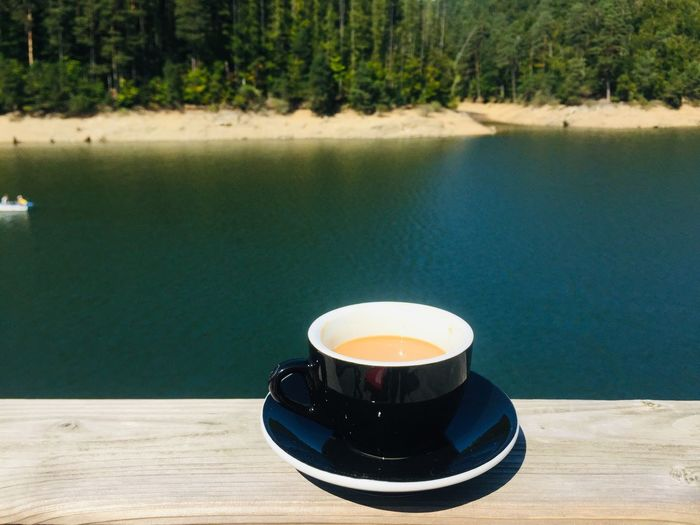 Cup of coffee placed on wooden table near a lake surrounded by green forest