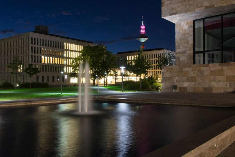 Fountain at goethe university of frankfurt against illuminated europaturm