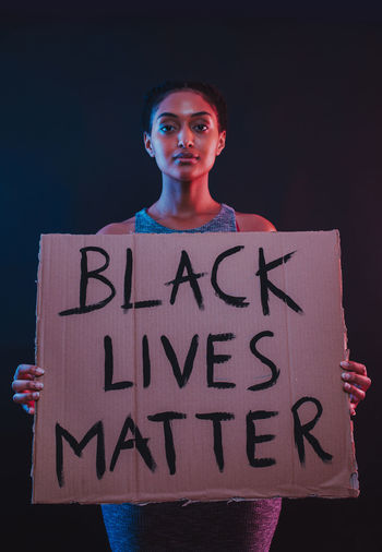Portrait of teenage girl standing against black background