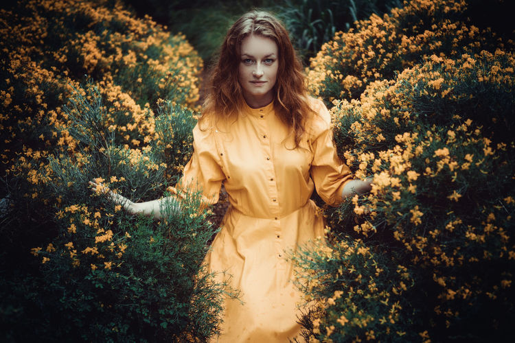 Young woman in a yellow dress in the middle of yellow flowers Beautiful Woman Beauty In Nature Flower Front View Lifestyles Looking At Camera Nature One Person Outdoors Portrait Real People Tree Young Adult Young Women