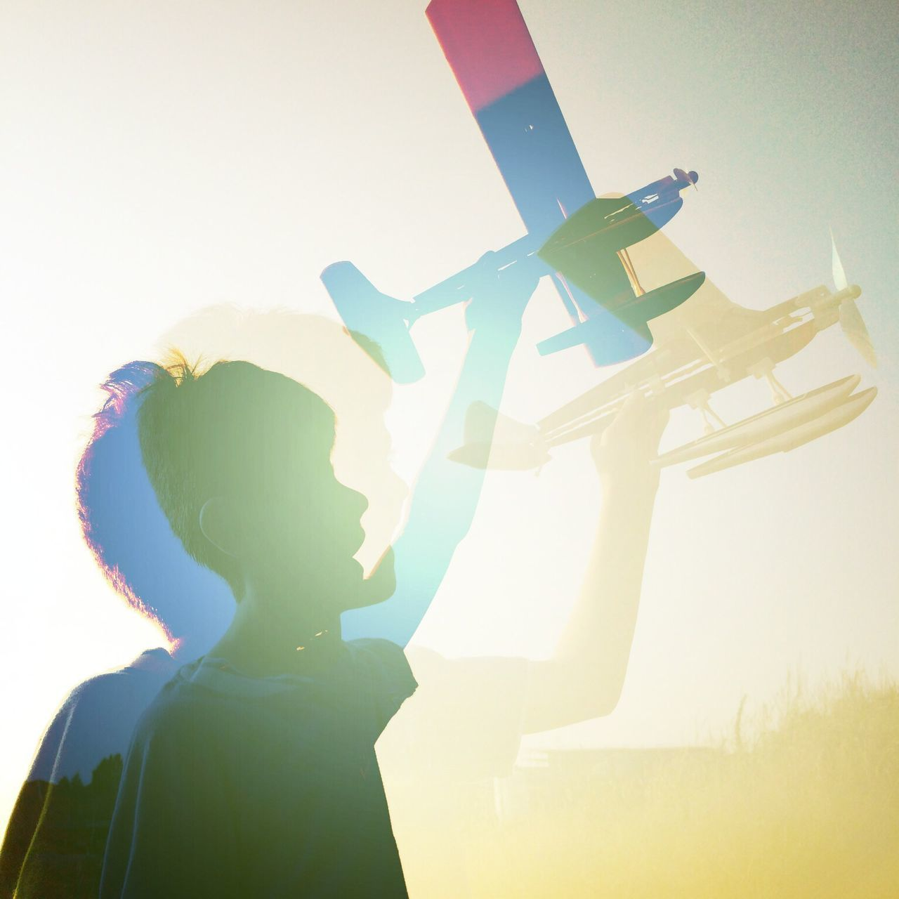 Digital composite image of boy holding airplane
